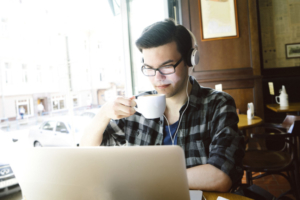 Cheerful young man using laptop in coffee shop.