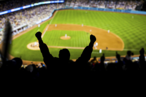 Fans raise their hands in excitement at a baseball game.